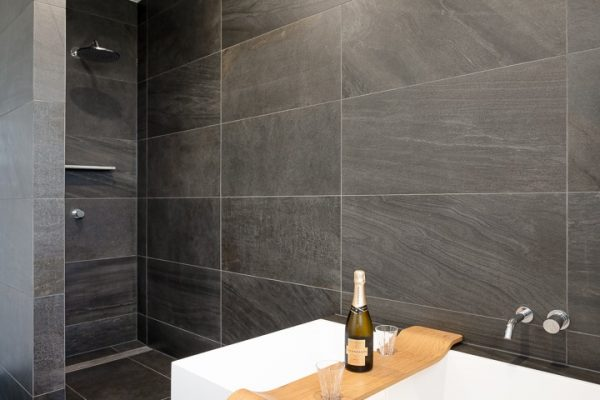 Bathroom tiled with black porcelain tiles